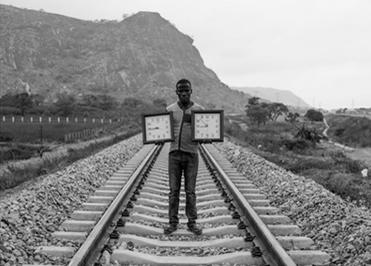 Fotodetail von Emeka Okereke, mann auf Zugleisen stehend mit zwei Wanduhren in den Händen, 2016